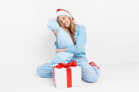 Christmas morning. Happy beautiful young girl, in Christmas pajamas and Santa hat, received a gift on Christmas day, on white background Stockfoto