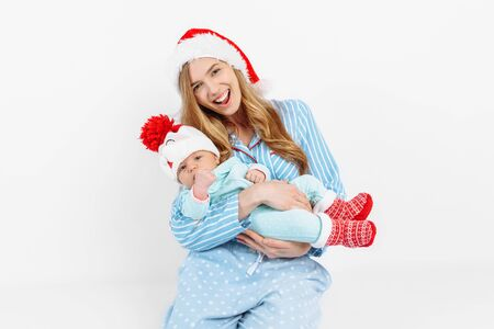 A young mother, on Christmas day gives a gift to a newborn child, a girl holds a baby in her arms in a Christmas hat, Christmas morning in the family, on a white background