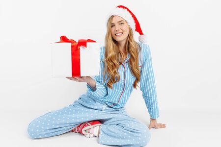 Christmas morning. Happy beautiful young girl, in Christmas pajamas and Santa hat, is happy to receive a gift, on white background