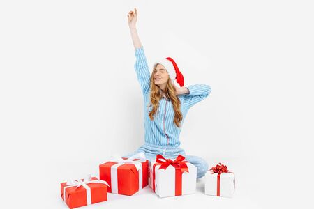 Christmas morning. Happy beautiful young girl, in Christmas pajamas and Santa hat, received many Christmas gifts, on white background