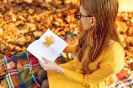 Attractive young female student in the autumn Park reading a book while sitting on a blanket, the girl is enjoying the warm Sunny weather Stockfoto