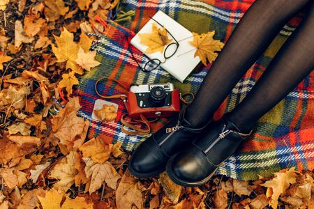 Checkered red and yellow plaid with fringe and autumn leaves, a book, glasses, and a camera, and a girls legs on the background of nature. Autumn outdoor recreation concept Stockfoto