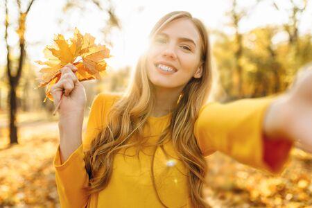 Feliz hermosa joven brillante toma selfie con hojas de otoño en el parque otoño Foto de archivo