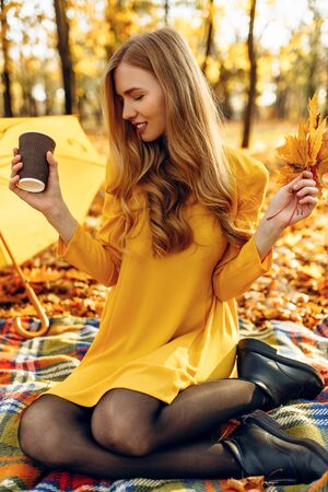 Beautiful young girl in autumn Park sitting on a blanket, holding a hot drink, enjoying the warm Sunny weather