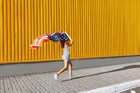 A young happy girl runs carefree with open arms around the city at the yellow wall, holding an American flag