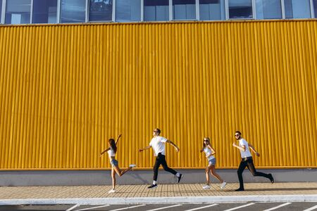 happy group of young people have fun while running and jumping in the city, against the yellow wall during sunset