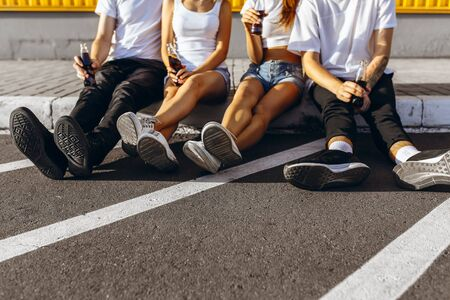 A group of young friends guys and girls hanging out in the city, cheerful friends sitting on the road at the yellow wall and having fun with drinks .