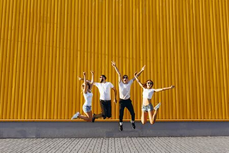 Happy young friends, men and women, have fun and jump around the city on the background of the yellow wall, depicting a gesture of victory