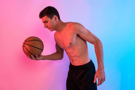 An image of a focused young sports man posing with a basketball, against a background of neon light holding a basketball.