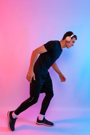 Full length young man with muscular body in headphones getting ready for a jog, in Studio background with red and blue neon light