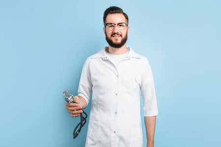 A young Intern doctor with a stethoscope in his hands stands on a light blue background Stock fotó
