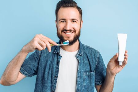 Happy young man with bristles, holding a brush and a tube of toothpaste, brushing his teeth immediately after waking up. Hygiene, morning routine and the concept of teeth whitening
