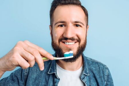 A young man with a toothbrush on a blue background, the concept of care for the oral cavity, the oral hygiene