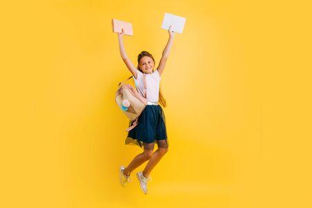 Happy teenage girl in school uniform, schoolgirl bounces merrily with books on a yellow background Foto de archivo