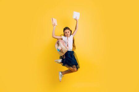 Happy teenage girl in school uniform, schoolgirl bounces merrily with books on a yellow background