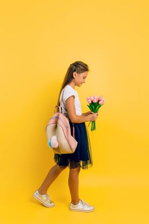 Cheerful teenage schoolgirl with a briefcase and a bouquet of tulips posing standing on a yellow background. Holiday concept