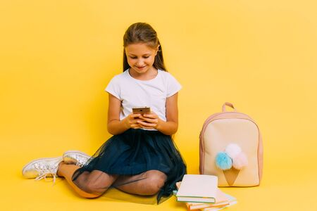 Modern happy teenage girl in school clothes with mobile phone on yellow isolated background