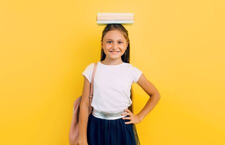 Beautiful smiling teenage girl in school clothes holding books on her head, on a yellow background