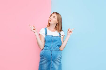 Gender of the child. A young, pensive pregnant woman in a denim jumpsuit, thinking about what gender the baby will be, stands on a pink and blue background
