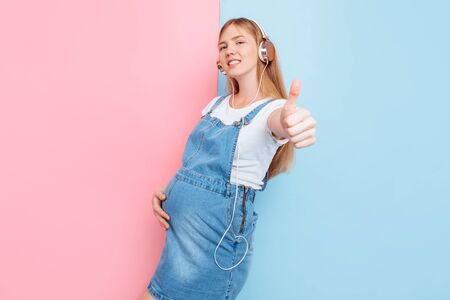 Happy cute beautiful young cheerful pregnant woman enjoys listening to music with headphones while standing on an isolated pink and blue background