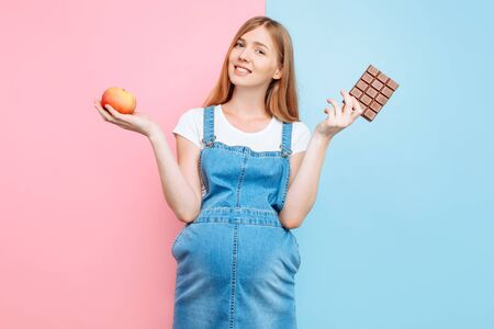 A perplexed pregnant woman chooses between sweets and fruit, holding an Apple and chocolate, standing on a pink and blue background