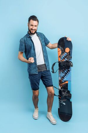 A happy man with a beard , wearing shorts and a shirt , holds a snowboard and shows a gesture of victory and success, standing on an isolated blue background