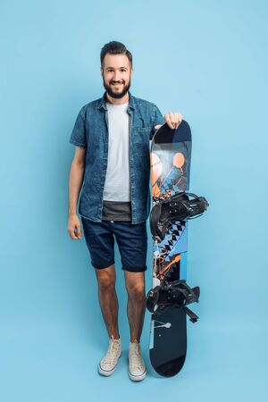 Happy attractive man with a beard wearing shorts and a shirt holding a snowboard isolated on a blue background