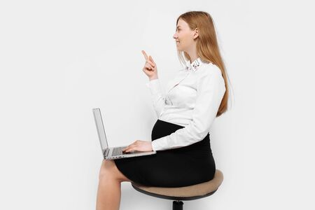 Image of a young pregnant businesswoman in glasses, a girl holding a laptop and pointing to an empty space in the background, sitting on a chair, on a white background Archivio Fotografico