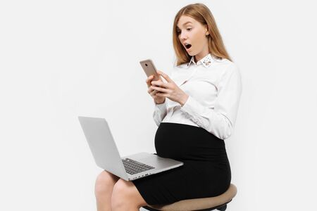 The image of a young pregnant businesswoman in glasses, shocked girl holding smartphone, looking at the screen, and holds the laptop while sitting on a chair, on a white background Archivio Fotografico