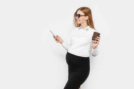 Image of a young pregnant businesswoman wearing glasses, a girl holding a smartphone and drinking coffee in a Cup, a break at work, on a white background Archivio Fotografico