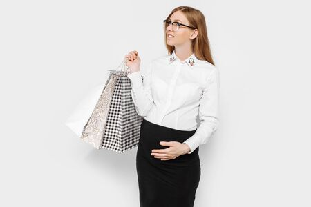 The image of a young pregnant businesswoman with glasses, happy girl holding shopping bags, shopping on a white background Archivio Fotografico