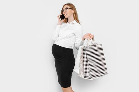 Image of young pregnant businesswoman wearing glasses, talking on phone, holding bags, shopping on white backg