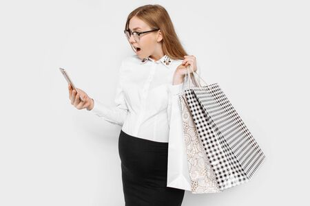 Image of young pregnant businesswoman wearing glasses holding smartphone and bags shopping on white background Archivio Fotografico