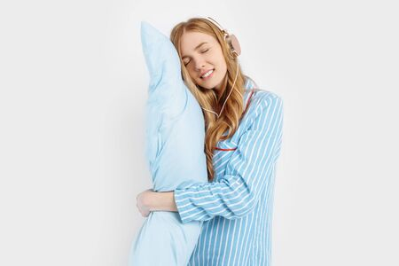 Happy attractive young girl in pajamas and with a soft pillow listens to music in headphones before going to bed on a white background