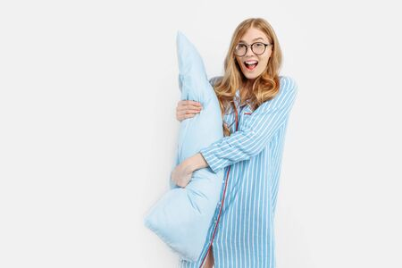 Portrait of happy beautiful girl dressed in homemade pajamas holding pillow and looking at camera isolated on white background Reklamní fotografie