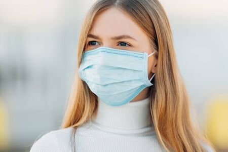 A young girl in the background of a building wears a face mask that protects against the spread of coronavirus disease. Close- up of a young woman with a surgical mask on her face against SARS-cov-2.