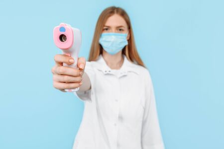 a female doctor, wearing a medical mask and white coat, uses a non- contact infrared forehead thermometer to check the patient's body temperature for symptoms of the virus against a blue background.