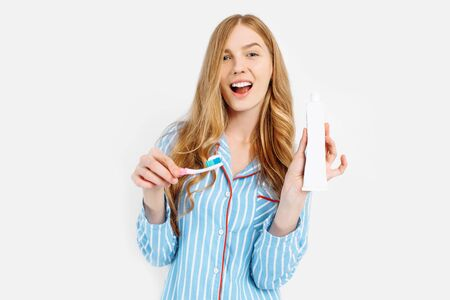 Portrait of a cute beautiful girl in pajamas and holding a tube of toothpaste isolated on a white background, white tubes of toothpaste close-up, isolated 版權商用圖片