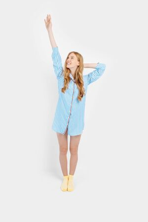 Portrait of beautiful pensive girl in pajamas holding pillow, dreamer before going to bed to see sweet dreams, on white background, a woman exercises in the morning in her pajamas