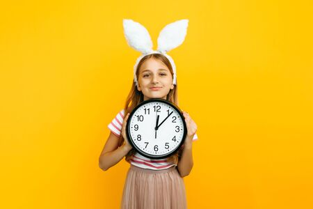 Happy beautiful girl on her head with rabbit ears, with a wall clock in her hands on a yellow background. Symbol of Easter and spring.