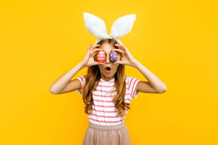 Shocked surprised beautiful girl on her head with rabbit ears and colorful Easter eggs in front of her eyes, on a yellow background. Symbol of Easter and spring.