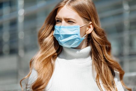 Beautiful young girl in a mask from coronovirus, student on the background of educational envy, women returning from work, remote work, covid-19