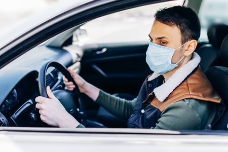 Beautiful young masked man sitting in a car, protective mask against coronavirus, driver on a city street during a coronavirus outbreak, covid-19