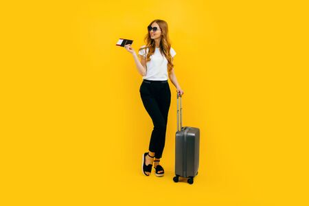 Happy beautiful woman, girl with a suitcase and passport with tickets on a yellow background. The concept of travel, business