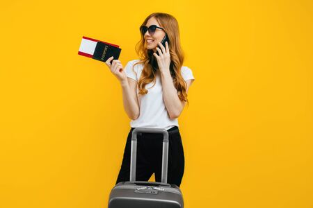 A happy young woman in dark glasses, talking on a mobile phone, standing with a suitcase and a passport with tickets on a yellow background. The concept of travel, business Imagens