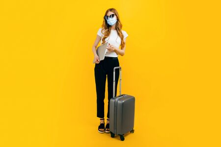 A young businesswoman with dark glasses, a protective medical mask on her face, a laptop and a suitcase on a yellow background. The concept of travel, trips abroad, quarantine and coronavirus