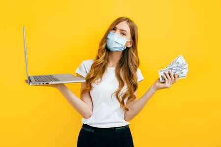 A young woman in a protective medical mask, using a laptop and holding cash dollar bills, on a yellow background. Concept of quarantine, coronavirus