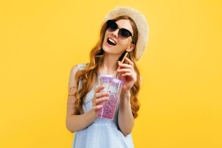 Happy beautiful girl in a hat and sunglasses with a refreshing summer cocktail on an isolated yellow background. Travel, vacation, summer Standard-Bild