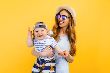 Happy family vacation in summer. Young happy mother holds a small child in her arms, on a yellow background. Family holidays, summer, travel