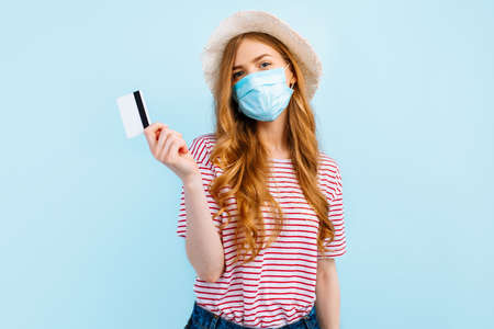 A girl in a summer hat wears a protective medical mask, holds a credit card, on a blue background. The concept of quarantine, coronavirus, shopping